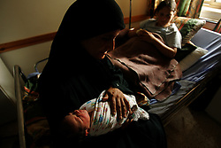 "Inas, the newborn daughter of Jawaher Ali Salah, 19, is comforted by her grandmother Jamila Abu Sarhan inside the Shepherd's Field Hospital in Bethlehem, Palestinian Territories, Nov. 15, 2004. The baby was born via cesarian section when she was breeched. Once the baby goes home and the family has gathered enough money, they will slaughter one sheep. When a boy is born, two sheep are killed in celebration. ""We are very poor, so all we can do right now is give sweets to our neighbors,"" said the father Ali Salah Tambre, 28. Ali used to work as a laborer in Israel but has been unemployed since the beginning of the second intifada."