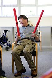 Day Service user with learning disability using rhythm sticks to keep time with music,