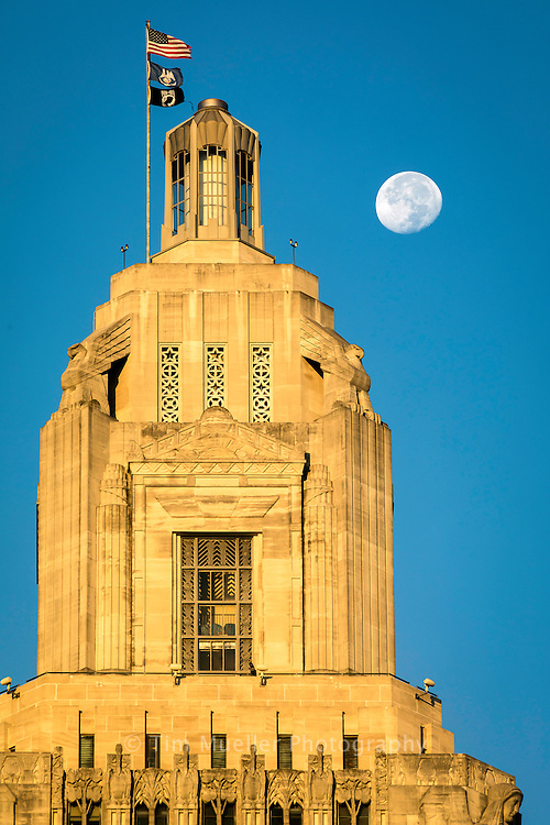 The moon in the waning gibbous phase sets over the Louisiana State Capital in Baton Rouge, La.