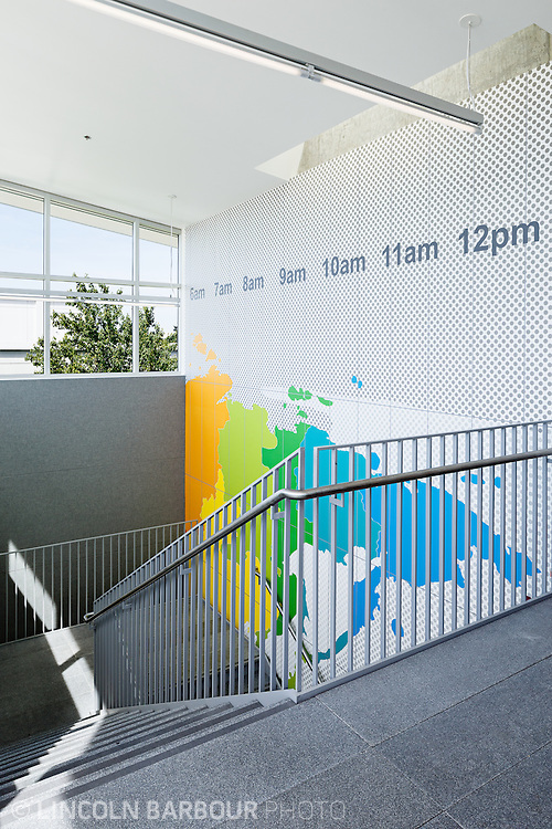 A stairwell inside of the PCC East Campus with a brightly colord map on the wall and what appears to be a modern sundial.