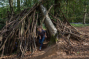 A seven year-old boy plays on his own inside a wooden den, on 23rd April 2017, in Wrington, North Somerset, England.