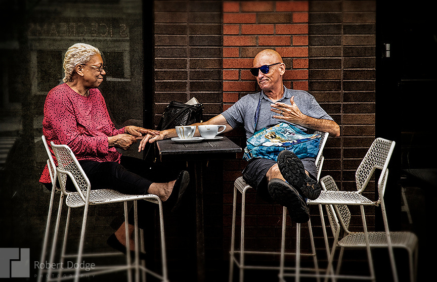 """Two friends share some special time together with the woman massaging her friend's arthritic hands. A dapper dandy makes his way up the street from grocery shopping -- perhaps eager to taste the goodies he just purchased. This image is from Robert Dodge """"Project: 14th and U Streets,"""" a look at the center of town in Washington, D.C. For info on publication or fine-art-, limited-edition prints, contact: Robert@RobertDodge.com."""