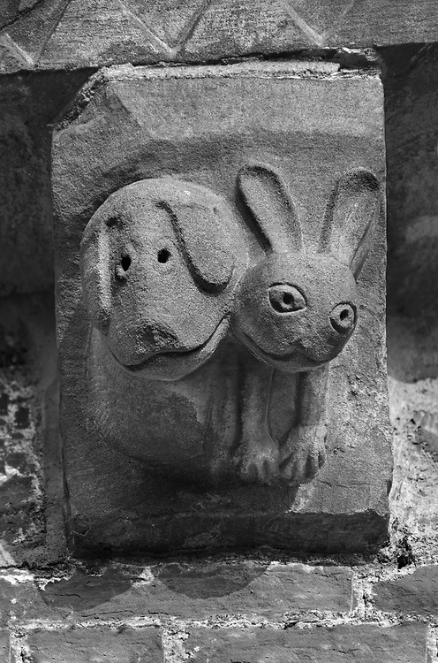 The Stone Bestiary - Black and white photo art print of Norman Romanesque exterior corbel no 33  -  sculpture of.very modern cartoon like hound and a hare. In the Bestiary dogs are like preachers who put men back on the right course of righteousness and the hare represents men who fear God and put their trust in the creator . The Norman Romanesque Church of St Mary and St David, Kilpeck Herefordshire, England. Built around 1140 .<br /> <br /> Visit our LANDSCAPE PHOTO ART PRINT COLLECTIONS for more wall art photos to browse https://funkystock.photoshelter.com/gallery-collection/Places-Landscape-Photo-art-Prints-by-Photographer-Paul-Williams/C00001WetsxVxNTo .<br /> <br /> By Photographer Paul E Williams