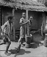 Girls pounding grain in a wooden pestle - West Nile, Moyo District, Uganda.