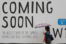"© licensed to London News Pictures. London, UK 08/07/2012. A woman walking past an advertisement reading ""Coming Soon"" under the rain today. Weather forecasts predict more rain to come this week. Photo credit: Tolga Akmen/LNP"