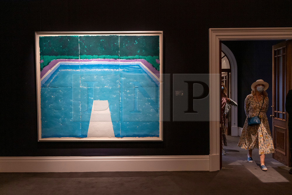 © Licensed to London News Pictures. 23/07/2020. London, UK.  A Sotheby's staff member views artwork titled Pool on a Cloudy Day with Rain (1978) by artist David Hockney with an estimate of £4-6 million. Works spanning over half a millennium of art history go on display at Sotheby's London ahead of a one-off auction on July 28. Titled 'Rembrandt to Richter', the sale will offer the very best from Old Masters, Impressionist & Modern Art, Modern & Post-War British Art and Contemporary Art – travelling from the Italian Renaissance through to Pop Art. Photo embargoed for usage until 24th July 2020 09:00. Photo credit: Ray Tang/LNP