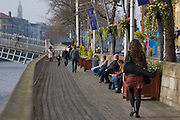 Red haired girl walking down the Liffey Boardwalk towards Ha'penny Bridge, Dublin, carrying violin case