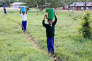 School children bring water to school. ICS Raleigh SWASH (school water, sanitation and hygiene plan) project. Mbulu, Manyara district, Tanzania. Working in partnership with the Diocese of Mbulu Development Department (DMDD); part of Caritas Tanzania.