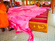 "24 JUNE 2017 - BANG KRUAI, NONTHABURI: Monks pull the pink sheets over people in coffins being reincarnated during a ""resurrection"" or rebirthing ceremony at Wat Ta Kien (also spelled Wat Tahkian), a Buddhist temple in the suburbs of Bangkok. People go to the temple to participate in a ""Resurrection Ceremony."" Thai Buddhists believe that connecting people by strings around their heads, which are connected to a web of strings suspended from the ceiling, amplifies the power of the prayer. Groups of people meet and pray with the temple's Buddhist monks. Then they lie in coffins, the monks pull a pink sheet over them, symbolizing their ritualistic death. The sheet is then pulled back, and people sit up in the coffin, symbolizing their ritualist rebirth. The ceremony is supposed to expunge bad karma and bad luck from a person's life and also get people used to the idea of the inevitability of death. Most times, one person lays in one coffin, but there is family sized coffin that can accommodate up to six people. The temple has been doing the resurrection ceremonies for about nine years.     PHOTO BY JACK KURTZ"