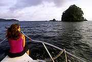 Woman on the front of a yacht during a trip to the west coast of Sao Tome island. The west coast has no road access so many visitors choose to have a boat day trip to visit the pristine beaches.