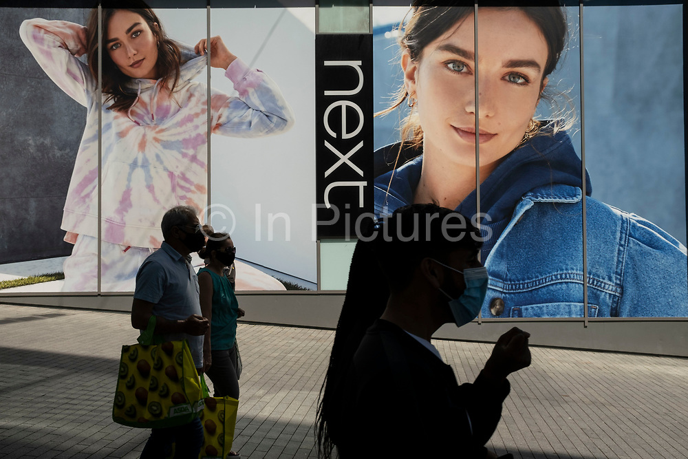 As the coronavirus restrictions continue and the government is about to announce an extension to the original freedom day planned for June, slowing the process of easing, more and more people begin to come to the city centre, seen here passing a large scale advertisement for Next on 15th June 2021 in Birmingham, United Kingdom. After months of lockdown, the first signs that life will start to get back to normal continue, with more people enjoying the company of others in public, while uncertainty continues for a projected further month, which is being dubbed The final push.