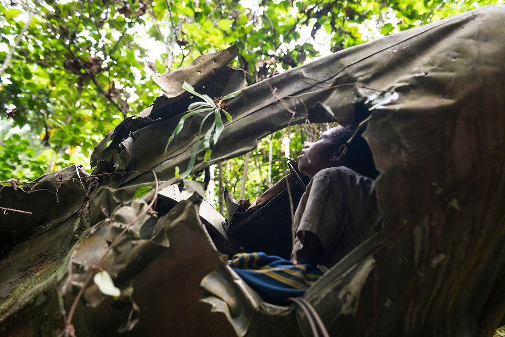 Ricky Muka sits in the tail section of an A-20 Havoc that crashed in the jungle near the Clay River in Papua New Guinea on April 5, 1944.<br /><br />(June 21, 2019)