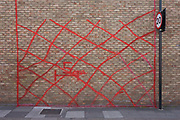 Sprayed marks on the outside wall of an industrial estate, marked for redevelopment in Loughborough Junction, a site for regeneration and gentrification of luxury flats in the south London borough of Lambeth. Criss-crossed over the brick wall are the aerosol markings to show a future demolition crew where to cut through this outer boundary. The gentrification process is spreading across many London boroughs, erasing industrial property, the home of small businesses and trades like carpentry - in favour of exclusive homes that command large deposits and rents that local Londoners cannot afford.