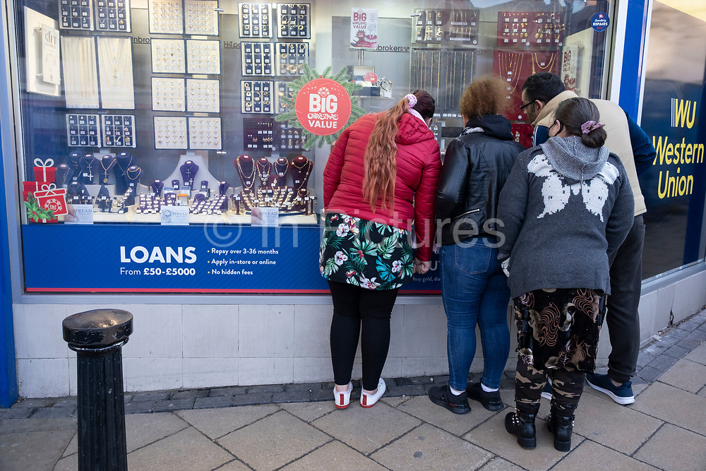 People looking into the window of H&T Pawnbrokers out and about visiting the shops in the City Centre as tier three / very high alert level of the Coronavirus tier system continues during the run up to Christmas on 14th December 2020 in Birmingham, United Kingdom. After 9 months of lockdown in various forms, people are used to navigating the rules of shopping safely as all non-essential shops try to increase their takings and onwards to the national economy.