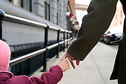 child holding on the finger of parent while walking
