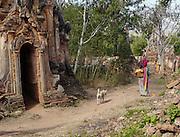 A  stray dog follows a vendor at the ruins of Nyaung Oak, Myanmar.