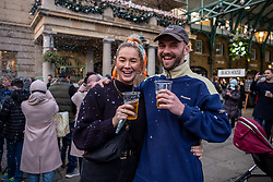 © Licensed to London News Pictures. 17/12/2020. London, UK. Beer drinkers enjoy the fake snow and a festive takeaway pint in Covent Garden, London today on the second day of Tier 3 for the capital. Today, Health Secretary Matt Hancock announced the latest updates on the government's tiering system as he plunged more of the South East of England including Surrey and Kent into Covid Tier 3 restrictions after health officials put pressure on the government not to reduce tier levels before Christmas. Yesterday, (Wednesday) London was put into Tier 3 restrictions after a new Covid-19 variant was discovered. Photo credit: Alex Lentati/LNP
