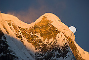 """The moon sets at sunrise over Annapurna South, seen from Annapurna South Base Camp (ABC, at 13,550 feet elevation), in the Himalaya mountain range of Nepal. Annapurna South (also known as Annapurna Dakshin, or Moditse; 23,684 feet / 7219 meters) was first climbed in 1964 by a Japanese expedition. Annapurna is Sanskrit for """"Goddess of the Harvests."""" In Hinduism, Annapurna is a goddess of fertility and agriculture and an avatar of Durga."""