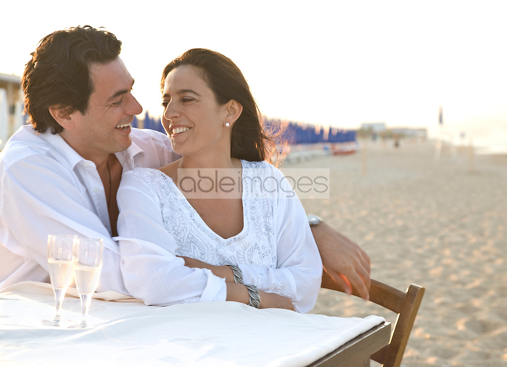 Couple on beach smiling and laughing and looking at each other