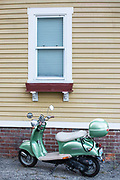 Icebear motor scooter parked by clapboard home in Newport, Rhode Island, USA