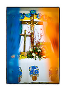 """SHOT 2/15/19 2:14:58 PM - The inside of a small capilla in the middle of the jungle near Chemuyil, Mexico. A pair of crosses featuring Jesus peek out from behind paper picado inside the capilla. Papel picado (""""perforated paper,"""" """"pecked paper"""") is a decorative craft made by cutting elaborate designs into sheets of tissue paper. (Photo by Marc Piscotty / © 2019)"""