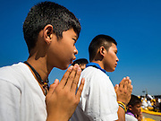 """02 JANUARY 2016 - KHLONG LUANG, PATHUM THANI, THAILAND: Boys pray at Wat Phra Dhammakaya on the first day of the 5th annual Dhammachai Dhutanaga (a dhutanga is a """"wandering"""" and translated as pilgrimage). More than 1,300 monks are participating pilgrimage through central Thailand. The purpose of the pilgrimage is to pay homage to the Buddha, preserve Buddhist culture, welcome the new year, and """"develop virtuous Buddhist youth leaders."""" Wat Phra Dhammakaya is the largest Buddhist temple in Thailand and the center of the Dhammakaya movement, a Buddhist sect founded in the 1970s. The monks are using busses on some parts of the pilgrimage this year after complaints about traffic jams caused by the monks walking along main highways.          PHOTO BY JACK KURTZ"""