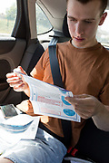 A young man in his twenties reads printed instructions after inserting a swab into his mouth to reach his tonsils and into his nasal passage from the rear seat of a car for a self-administered Coronavirus COVID-19 test in south London. There are four steps to the self-administered Covid-19 test inserting a swab into the nose and throat which the public works through in their car, windows up and all communications with army personnel via phone, in a south London leisure centre, on 2nd June 2020, in London, England. The kit provided consists of a booklet, plastic bag, swab, vial, bar codes and a sealable biohazard bag. The swab sample is taken from the back of the throat and nasal passage with the contents sealed and returned to soldiers through a narrow window. The whole process takes between 5-10mins with results available within 48hrs.