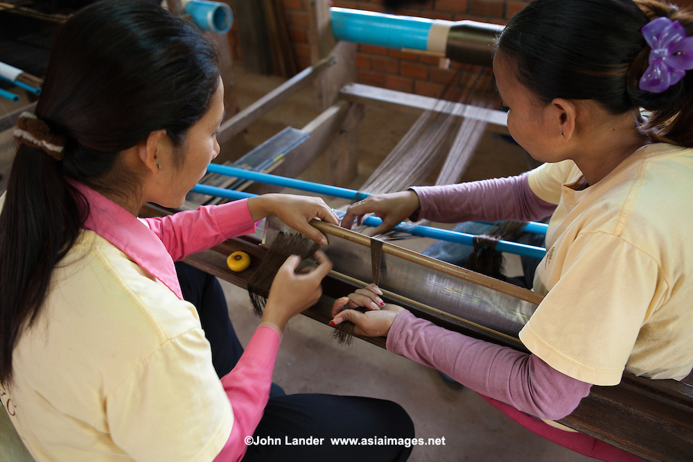"""Silk Farm at Artisans d'Angkor - a group trained by the Chantiers Écoles de Formation Professionnelle. Located in Siem Reap, Cambodia, with two training schools. An initiative of the National Cambodian Institutions, the French Foreign Ministry and the European Union, Chantiers Ecoles de Formation Professionnelle provides unschooled rural youth with free vocational training programs, while Artisans d'Angkor provides them a professional, economic and social integration into providing a service for their locale.  Its objectives are to support and promote Khmer art and culture, educating local youth, and provide jobs to youth interested in traditional crafts.  The Artisan's centre, established to perpetuate the art and culture of the World Heritage Site of Angkor through training the present generation of local youth in the disciplines of metal working, silk weaving, and wood and stone carving had the distinction of the artisans of the institute won the award """"Seal of Excellence for Handicrafts"""" in a competition organized by UNESCO."""