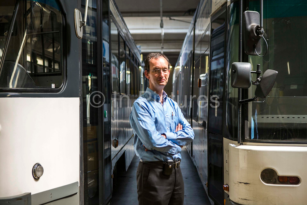 Portrait of Patrick De Boeuf, Chief Executive of De Lijn proudly stands in front of two modern electric public transport trams in Gentbrugge, Ghent, Belgium.  The tramcars have been modernized with innovative technology to reduce their electricity consumption.