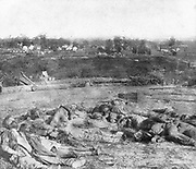 The Gathered Confederate Dead Before Battery Robinett taken the morning after their desperate attempt to carry the works by assault. No man can look at this awful picture and wish to go to war. These men, a few hours before, were full of life and hope and courage. Without the two last qualities they would not be lying as they are pictured here. In the very foreground, on the left, lies their leader, Colonel Rogers, and almost resting on his shoulder is the body of the gallant Colonel Ross. from the book ' The Civil war through the camera ' hundreds of vivid photographs actually taken in Civil war times, sixteen reproductions in color of famous war paintings. The new text history by Henry W. Elson. A. complete illustrated history of the Civil war
