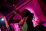 Male Brazilian singer with dreadlocks and microphone, pink lighting in a club. Digital Dubs dub reggae dancehall soundsystem at Leviano Bar, Lapa, Rio de Janeiro, Brazil