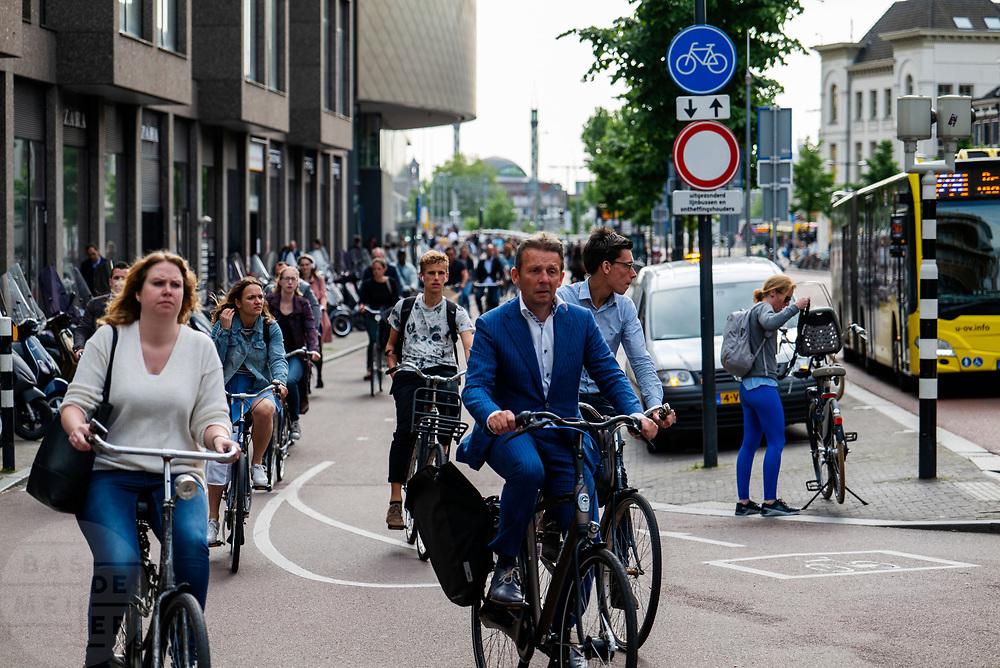 In Utrecht rijdt een grote stroom fietsers over het fietspad langs het Vredenburg tijdens de avondspits.<br /> <br /> In Utrecht cyclists ride at the bike lane near Vredenburg.