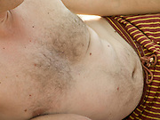 close up of a man?s belly while laying on it site at the beach