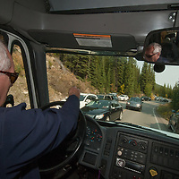 A bus driver navigates through double parked cars near Moraine Lake during a holiday weekend in Banff National Park, Alberta, Canada.
