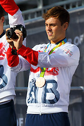 © Licensed to London News Pictures. 18/10/2016. London, UK. Bronze medalist diver TOM DALEY takes a picture of the crowd as Olympic and Paralympic athletes, who competed in the Rio 2016 Olympics receive hero's welcome in Trafalgar Square on Tuesday, 10 October 2016. Photo credit: Tolga Akmen/LNP