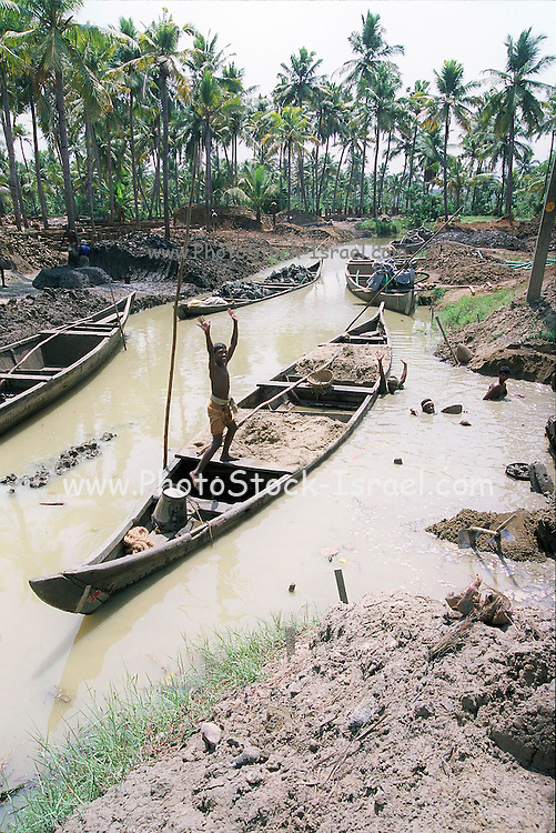 Men removing clay from the river at a brick production site India, Kerala, a state on the tropical coast of south west India