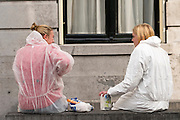 In Utrecht zitten twee meisjes in beschermende kleding en verfspullen op een muur voor het stadhuis.<br /> <br /> In Utrecht two girls in protective clothes and painting materials sit in front of the town hall on a wall.