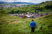 """Milan (front) just came back to his native Slovakia after living and working for a longer time in the UK and is since then unemployed (2014). The Roma part of the district """"Podsadek"""" in eastern Slovakia, located in a little valley. The city of Stara Lubovna (in the back) is located about 100 km from Kosice in northeast Slovakia. The town has a population of 16350, of whom 2 060 (13%) are of Roma origin. The majority of Roma live in the Podsadek district, where 980 (74%) out of 1330 inhabitants are Roma."""