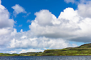 Puffy white Cumulus cloud formation above Dunvegan Loch, Isle of Skye, Western Scotland