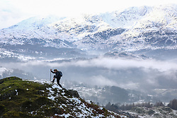 © Licensed to London News Pictures. 20/01/2019. Lake District, UK. A woman climbs near the summit of Loughrigg Fell in the Lake District as the surrounding mountains are covered in snow and fog fills the valleys during cold weather. Photo credit : Tom Nicholson/LNP