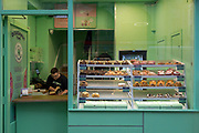 As the Coronavirus pandemic spreads across the UK, businesses and entertainment venues not already closed with the threat of job losses, struggle to stay open with growing rumours of a lockdown and travel restrictions around the capital. As Londoners start to work from home, shops like Doughnut Time experience a lack of trade where an employee passes time by reading his book, on 19th March 2020, in London, England.