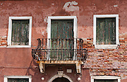 "Balcony, windows, shutters. Burano, known for knitted lacework, fishing, and colorfully painted houses, is a small archipelago of four islands linked by bridges in the Venetian Lagoon, northern Italy, Europe. Burano's traditional house colors are strictly regulated by government. The Romans may have been first to settle Burano. Romantic Venice (Venezia), ""City of Canals,"" stretches across 117 small islands in the marshy Venetian Lagoon along the Adriatic Sea in northeast Italy, between the mouths of the Po (south) and Piave (north) Rivers. Venice and the Venetian Lagoon are honored on UNESCO's World Heritage List."