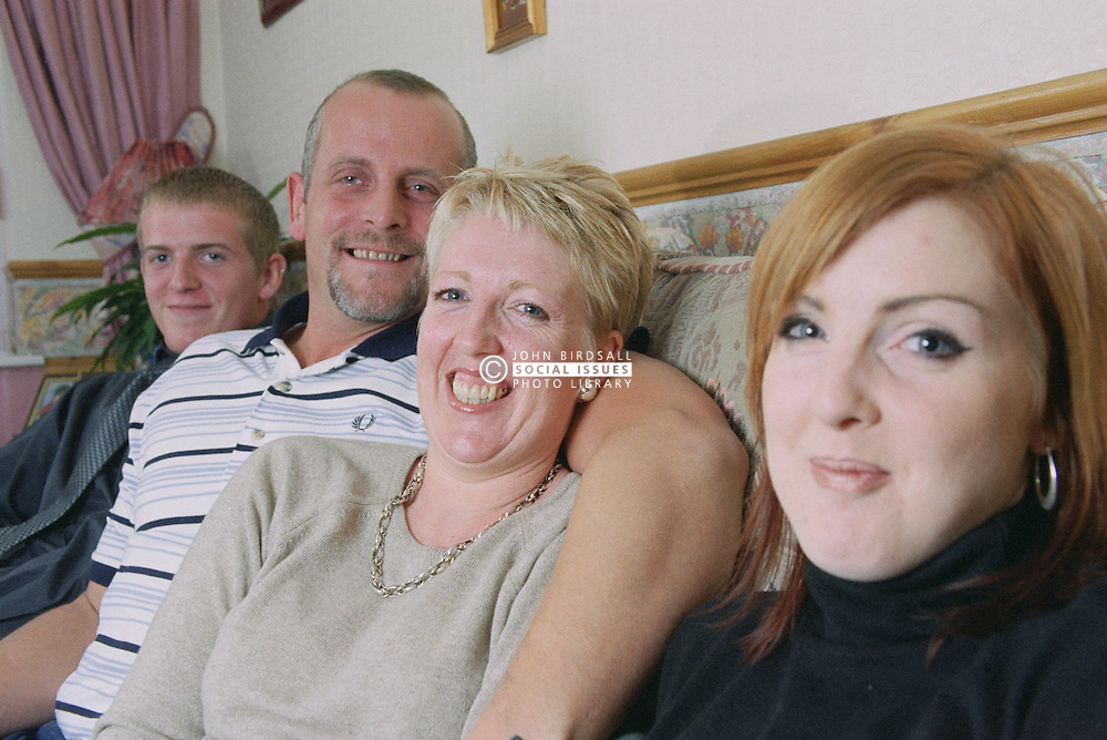 Mother and father sitting on sofa with teenage children,