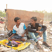 Two garbage collector takes a break. Located next to a lake, a visit to one of the main garbage dump in Kolkata. With 15 millions population in 2019 and growing, the city of Calcutta is a typical case of expansion through uncontrolled urbanization.