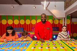 © Licensed to London News Pictures. 27/10/2021. LONDON, UK.  Local children join award-winning artist and designer Yinka Ilori as he unveils his 'Launderette of Dreams', a new installation where he has reimagined a community launderette in his signature colourful style. Made from over 200,000 LEGO bricks, the installation forms part of the LEGO Group's Rebuild the World campaign that celebrates children as masters of creative problem solving.  It can be found in Bethnal Green Rd, Shoreditch, 28 October to 6 November 2021..  Photo credit: Stephen Chung/LNP