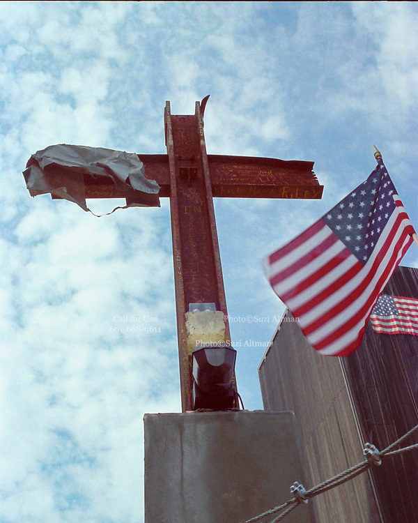 """The Miracle Cross at Ground Zero in New York City. The Cross was formed when the buildings collapsed and found by rescue workers and erected on the site as a memorial to those who died in the attack on The World Trade Center. Through my eyes and with my camera I am able to see the world we live in, and try to bring things into focus. Photography preserves my vision of what """"I see"""" at a specific time and place- a moment. Creating a bond between  me and my subject and capturing and emotion for eternity. Having lived and worked in New York City for over 15 years when 911 happened. I had to go and """"see"""" with my camera what lower Manhattan was like after this horrific attack on our Nation. The World Trade Center owned the skyline in lower Manhattan making it feel more like a canyon. After the Twin Towers fell, and I saw with my own eyes and camera the destruction, I realized what little land they actually sat on. The Twin Towers may not have occupied a large plot of land but they now touched everyones life. Photo©SuziAltman"""