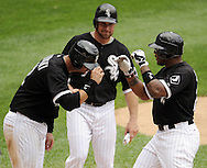CHICAGO - JULY 11:  Andruw Jones #25 is greeted by A.J. Pierzynski #12 and Mark Kotsay #7 of the Chicago White Sox at home plate after hitting Jones hit his 400th career home run off of Anthony Lerew #54 of the Kansas City Royals in the third inning on July 11, 2010 at U.S. Cellular Field in Chicago, Illinois.  The White Sox defeated the Royals 15-5.  (Photo by Ron Vesely)