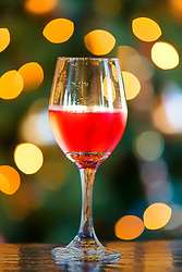 A glass of red wine glows in front of the Christmas tree lights