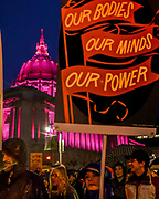 """Marchers pass from the pink-glowing San Francisco City Hall as rain falls and evening sets in. A woman holds a sign reading, """"Our bodies, our minds, our power."""""""