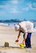 Elderly Man Making Sandcastles on a Beach